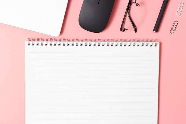 Lugar de trabajo moderno, bloc de notas para computadora portátil y accesorios en rosa, vista superior, espacio de copia Foto Premium