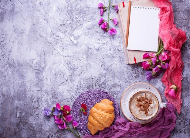 Lugar de trabajo de las niñas. café, croissants, flor y cuaderno. vista superior Foto Premium