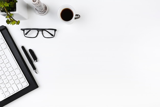 Lugar de trabajo de oficina con teclado y gafas Foto gratis
