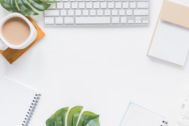 Lugar de trabajo con teclado, cuadernos y taza de café. Foto gratis