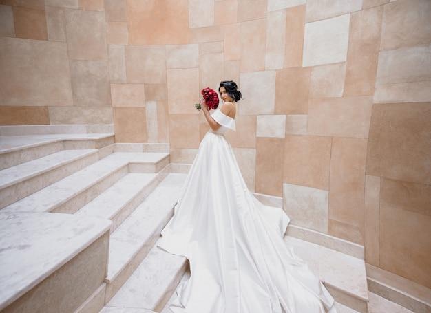 Lujosa novia morena caucásica está de pie en las escaleras cerca del muro de piedra y sosteniendo peonías rojas ramo de novia Foto gratis