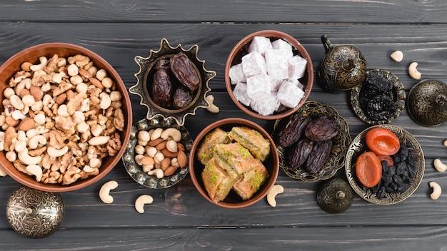 Lukum; fechas; frutas secas; baklava y nueces en tazón de tierra y metálico en el escritorio de madera Foto gratis