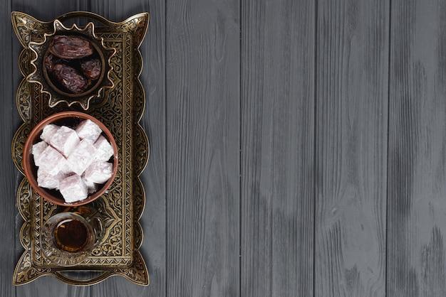 Lukum de postre turco ramadán; té y dátiles en bandeja metálica grabada sobre la superficie de madera negra Foto gratis