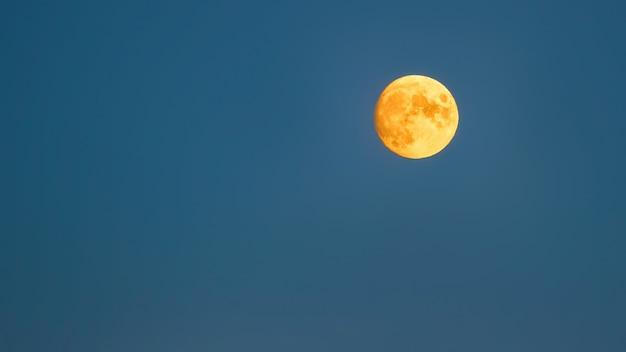 Luna llena amarilla sobre un cielo azul Foto gratis