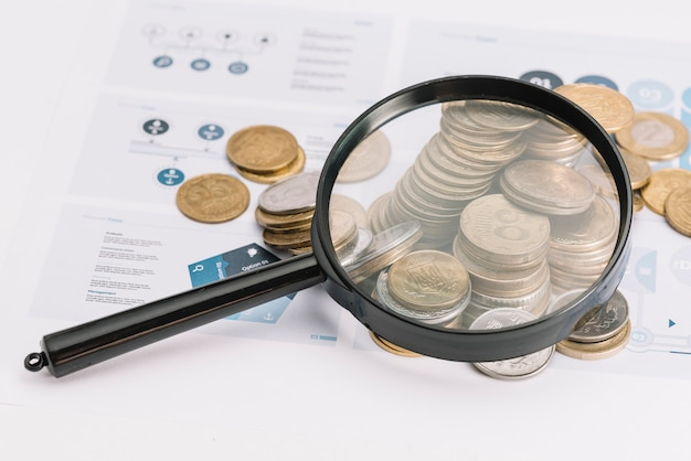 Lupa sobre las monedas caídas en plantilla de infografía Foto gratis