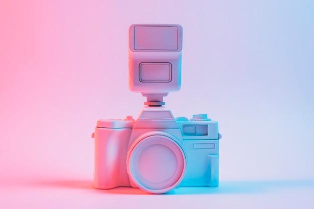 Luz azul en la cámara pintada de color rosa contra el telón de fondo de color rosa Foto gratis