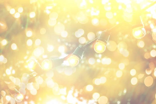 Luz bokeh borrosa en la puesta de sol con decoración de luces de cadena amarilla en restaurante de playa Foto Premium