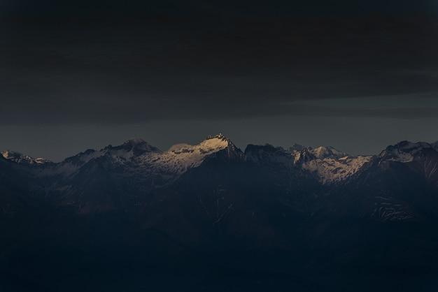 La luz del sol brillando en la cima de una montaña al atardecer con cielo nublado oscuro Foto gratis