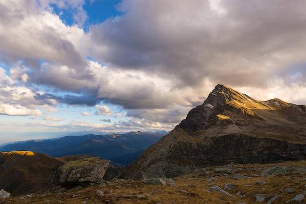 Luz del sol en los picos de las montañas del valle alpino y nubes escénicas Foto Premium