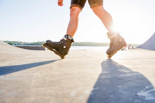 La luz del sol sobre la persona de patinaje en el parque de patinaje Foto gratis