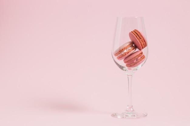 Macarons de colores sobre fondo rosa Foto Premium