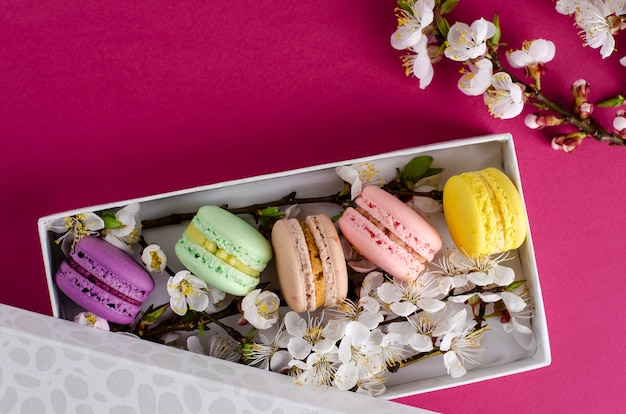 Macarrones frescos en una caja de regalo con flores de albaricoquero Foto Premium