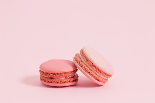 Macarrones o macaron franceses dulces y coloridos en el fondo rosado, postre. Foto Premium