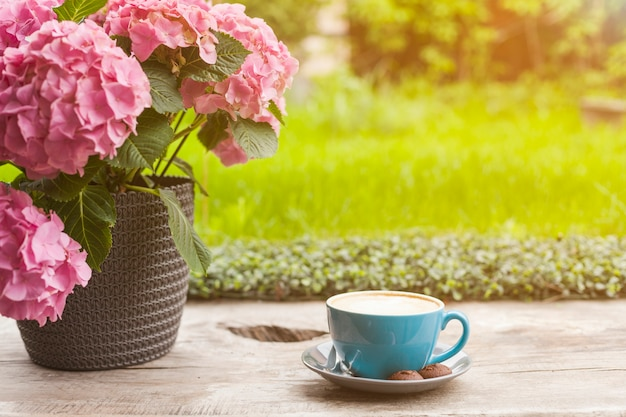 Maceta rosada hermosa y taza de café en superficie de madera Foto gratis