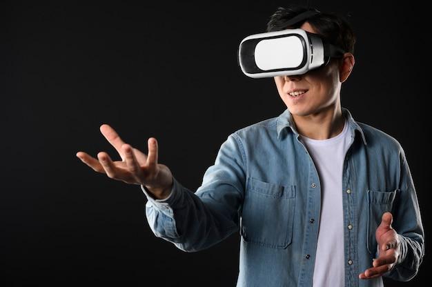 Macho de ángulo bajo con casco de realidad virtual Foto gratis