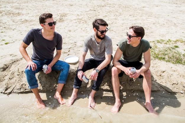 Machos descalzos charlando en la playa de arena Foto gratis