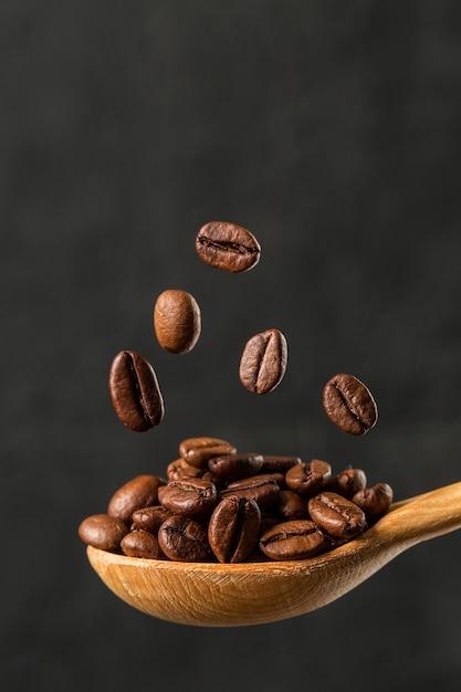Macro caída de grano de café sobre fondo gris Foto Premium