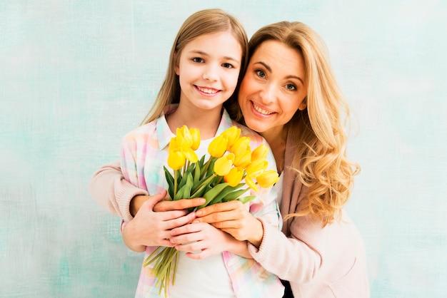 Madre abrazando hija y sosteniendo tulipanes Foto gratis