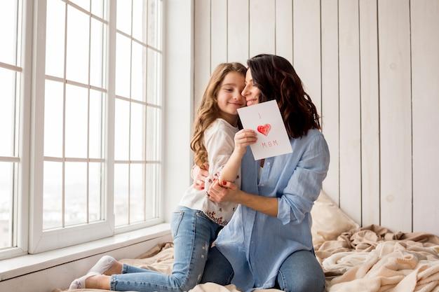 Madre abrazando a linda hija con tarjeta de felicitación Foto gratis