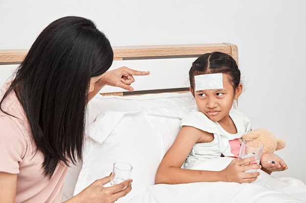 Madre alimentación jarabe de medicina para niña Foto Premium