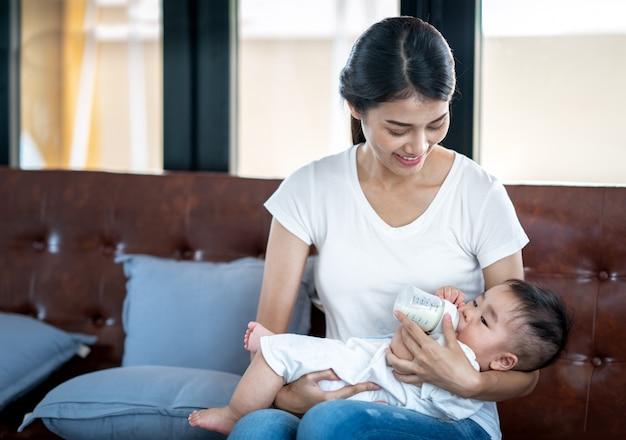 Madre asiática alimentando con leche a su bebé por biberón Foto Premium