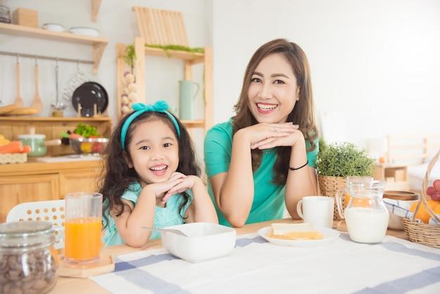 Madre asiática hermosa e hija que desayunan junto en casa por la mañana Foto Premium