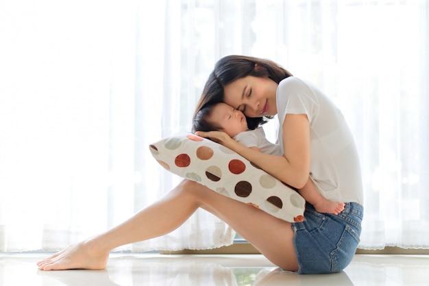 Madre asiática que celebra a su bebé en sus brazos que se sientan en casa. Foto Premium