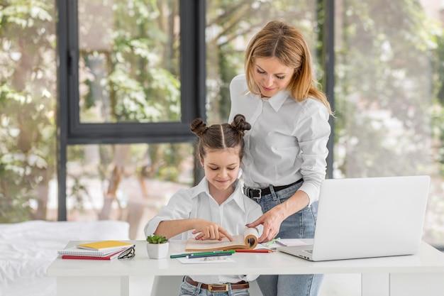 Madre ayudando a su hija a estudiar Foto gratis