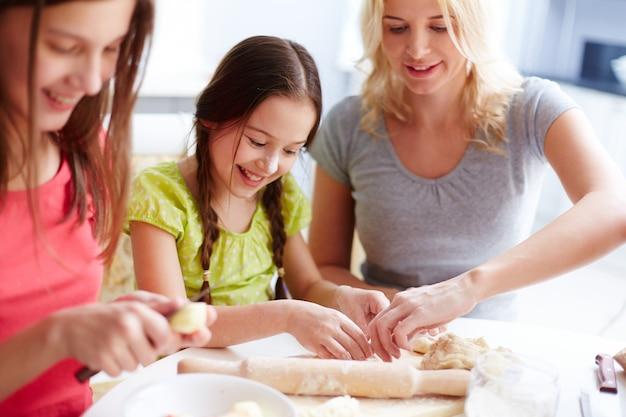 Madre ayudando a su hija con la masa de pizza Foto gratis