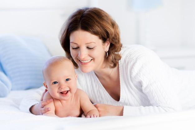 Madre y bebé en una cama blanca Foto Premium