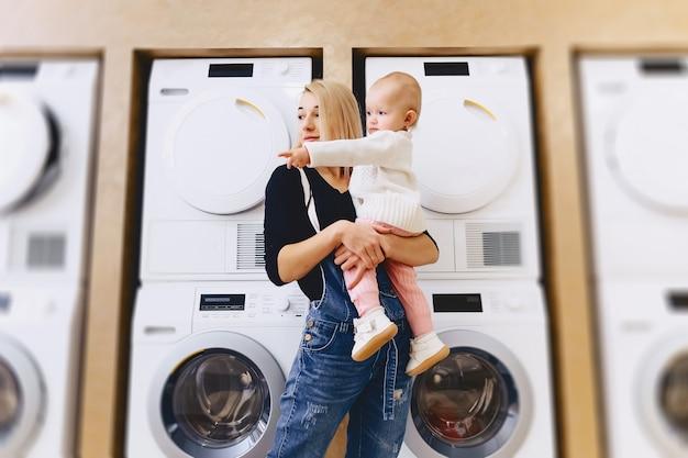 Madre con bebé en el fondo de lavadoras Foto Premium