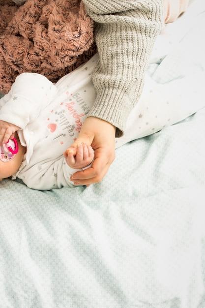 Madre y bebé tomados de la mano en la cama Foto gratis