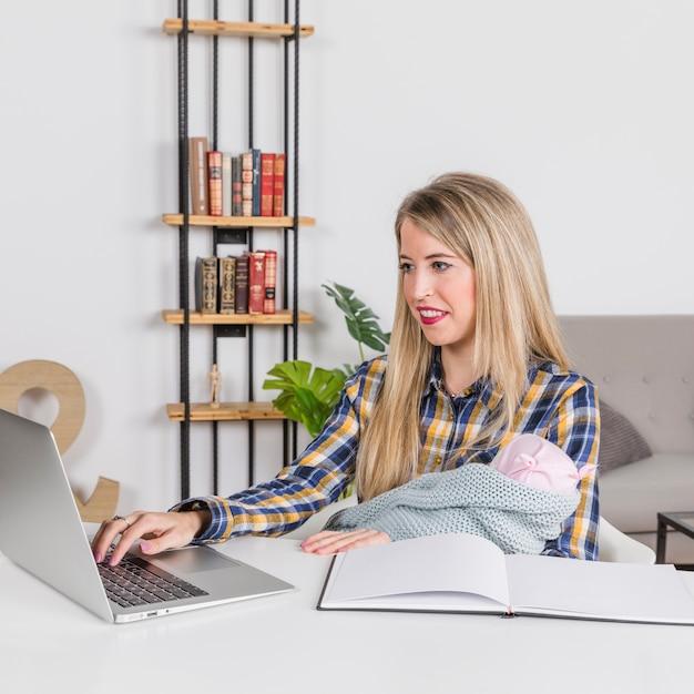 Madre con bebé trabajando con laptop en casa Foto gratis