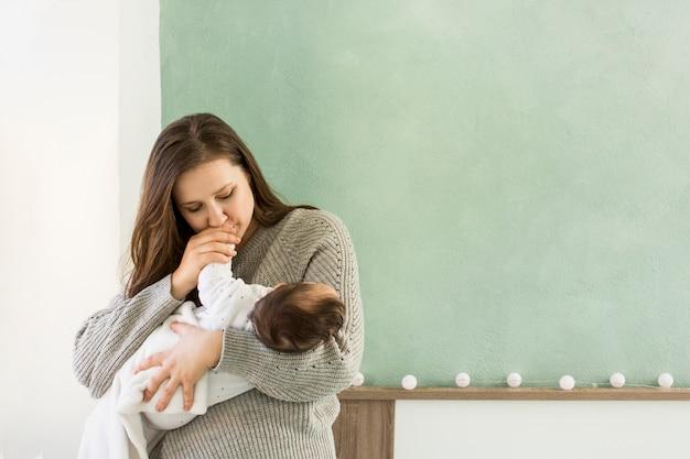 Madre besando la mano del bebé en brazos Foto gratis