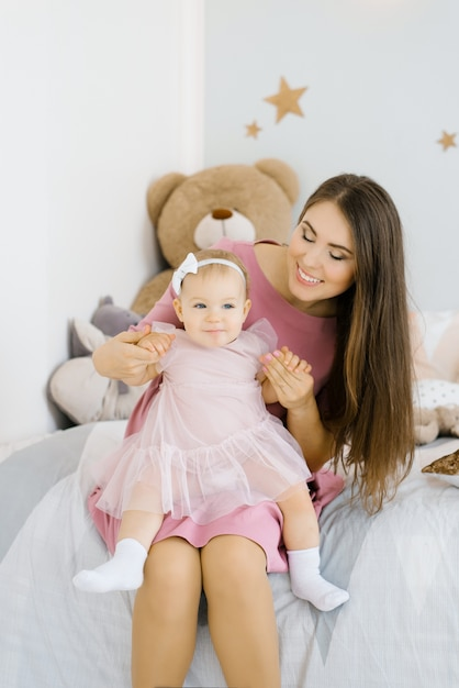 Una madre caucásica pone a su hija de un año en su regazo y la mira en la habitación de los niños en la casa y sonríe Foto Premium