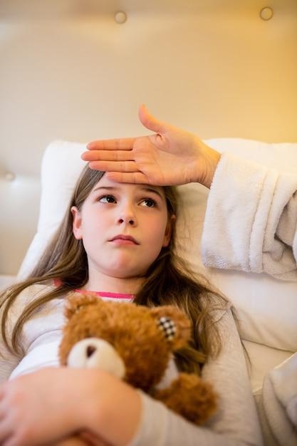 Madre de comprobar la fiebre de su hija en el dormitorio Foto gratis
