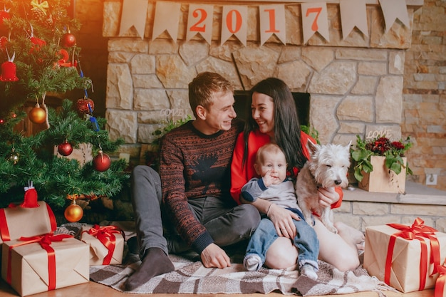 Madre con su bebé y su perro en brazos en navidad Foto Gratis