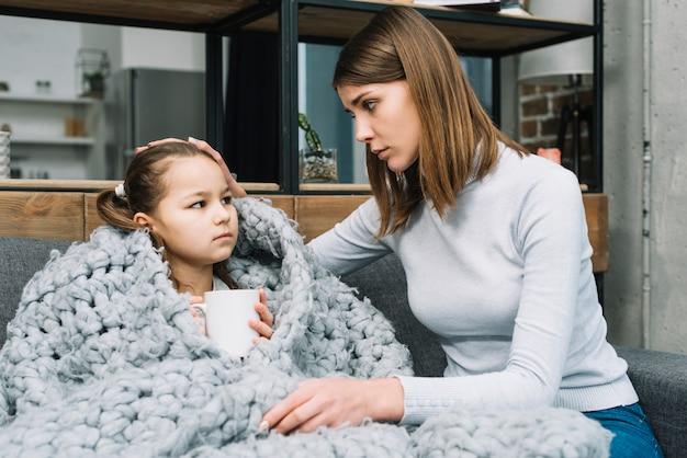 Madre cuidando a su hija cubierta con una bufanda de lana gris que sufre de fiebre. Foto gratis