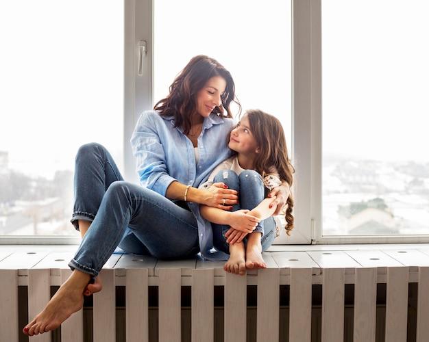 Madre e hija abrazando en el alféizar de la ventana Foto gratis