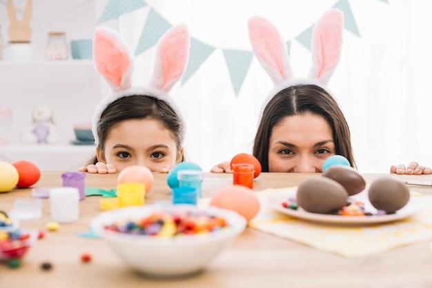 Madre e hija asomándose por detrás de la mesa con huevos de pascua; confitería y colores Foto gratis