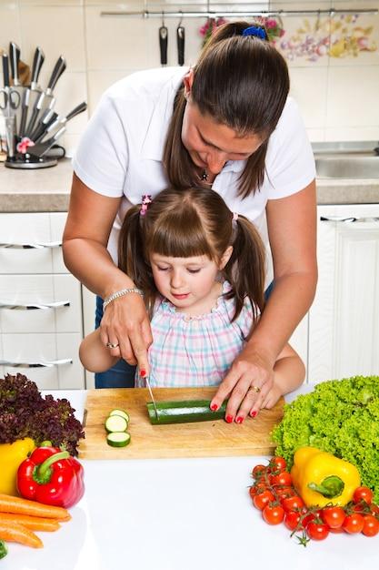 Madre e hija en la cocina preparando verduras Foto Premium