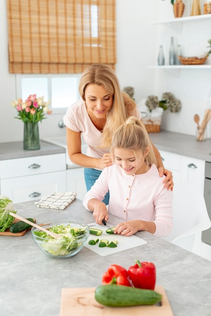 Madre e hija cortando pepinos Foto gratis