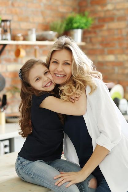 Madre e hija dándose un fuerte abrazo Foto gratis