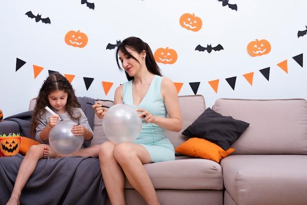 Madre e hija dibujando en globos Foto gratis