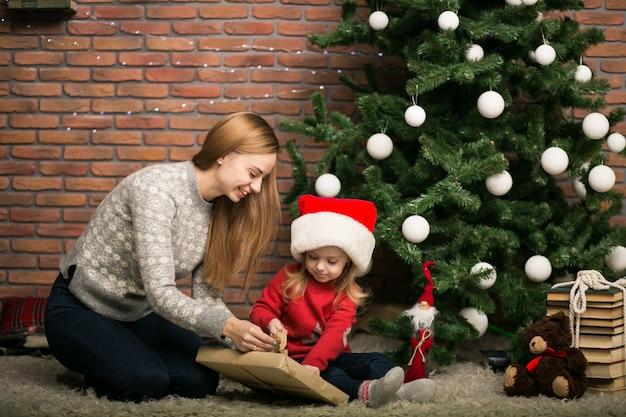 Madre e hija embalaje regalos por el rbol de navidad - Regalos navidad mama ...
