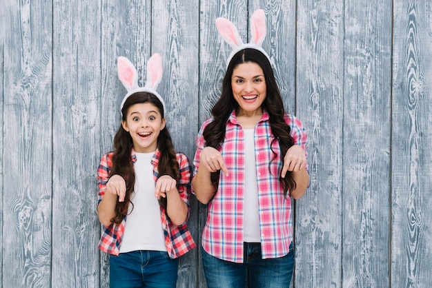 Madre e hija emocionadas con las orejas del conejito que señalan el dedo hacia abajo contra el contexto de madera Foto gratis