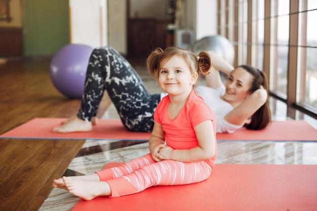Madre e hija entrenando en un gimnasio Foto gratis