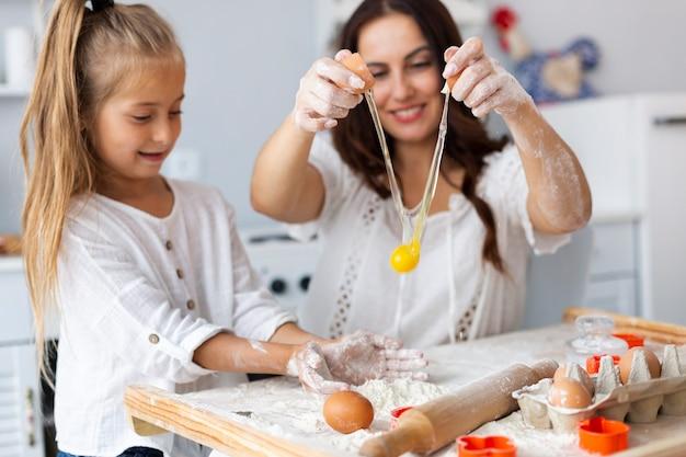 Madre e hija frenando huevos Foto gratis