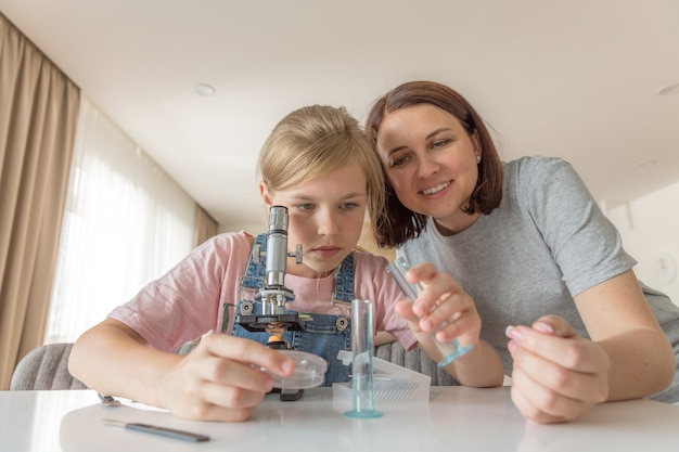 Madre e hija hacen experimentos químicos con microscopio en casa Foto Premium