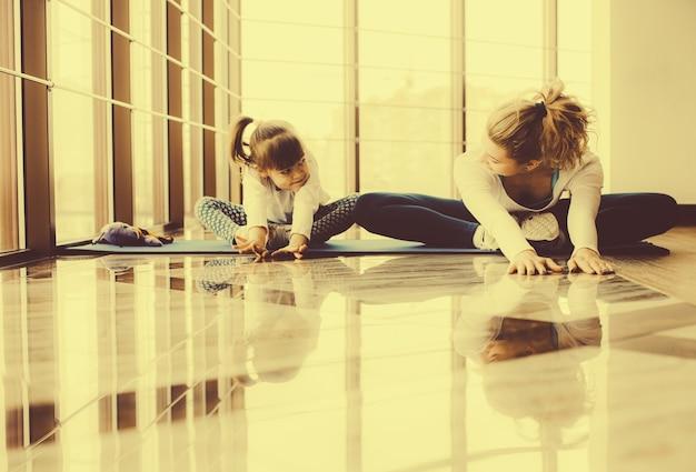 Madre e hija haciendo yoga en casa Foto gratis